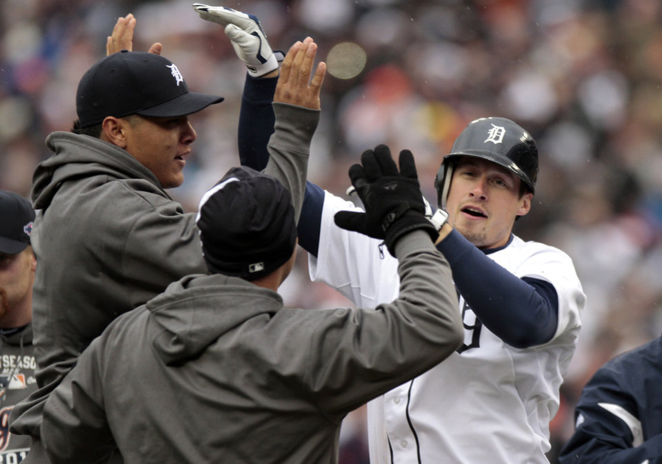 Detroit Tigers' Don Kelly is congratulated by teammates after hitting a sacrifice fly to right to score teammate Omar Infante in the ninth inning of Game 2 of the American League division baseball series against the Oakland Athletics, Sunday, Oct. 7, 2012, in Detroit. (AP Photo/Duane Burleson)