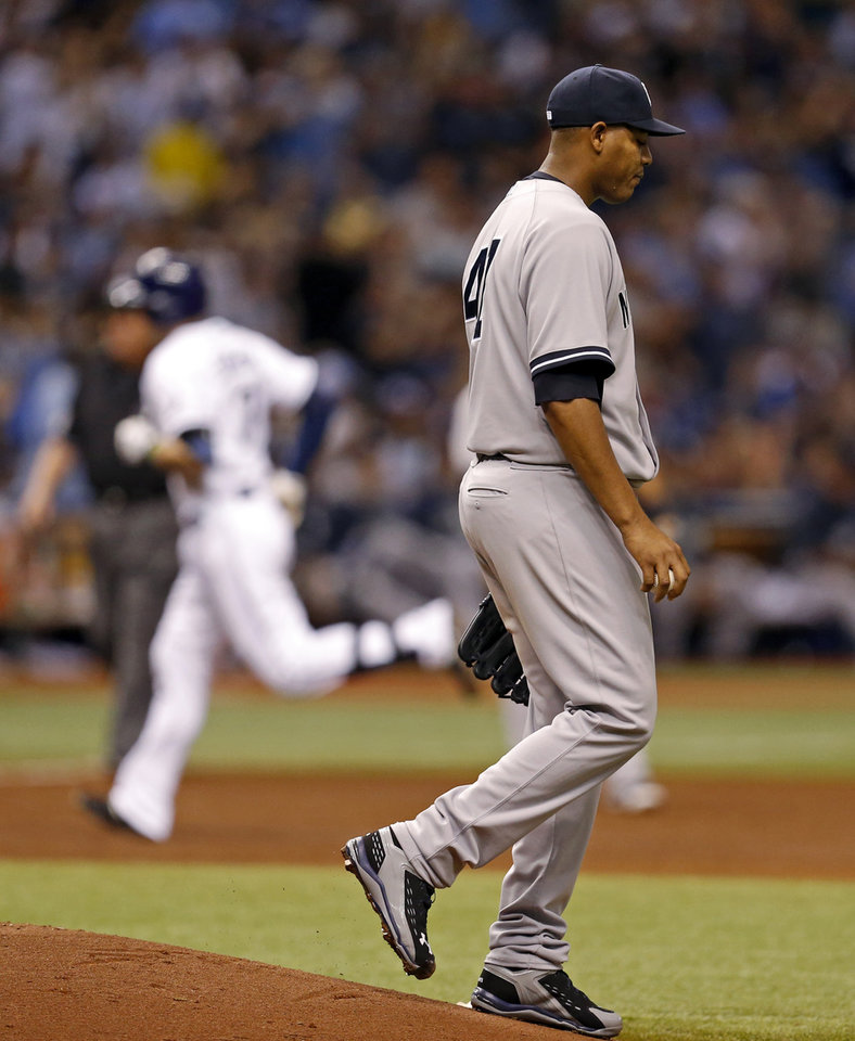 Photo - New York Yankees starting pitcher Ivan Nova reacts to giving up a two-run home run to Tampa Bay Rays' Evan Longoria during the third inning of a baseball game, Saturday, April 19, 2014, in St. Petersburg, Fla. (AP Photo/Mike Carlson)