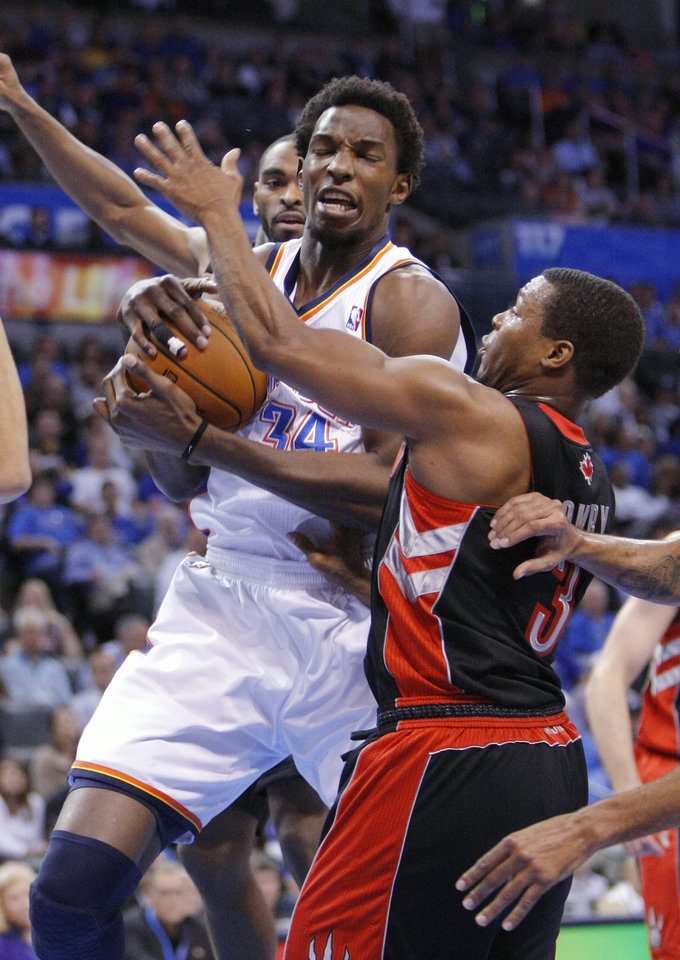 Oklahoma City Thunder center Hasheem Thabeet (34) grabs a rebound from Toronto Raptors guard Kyle Lowry (3) during the first quarter of an NBA basketball game in Oklahoma City, Tuesday, Nov. 6, 2012. (AP Photo/Alonzo Adams)