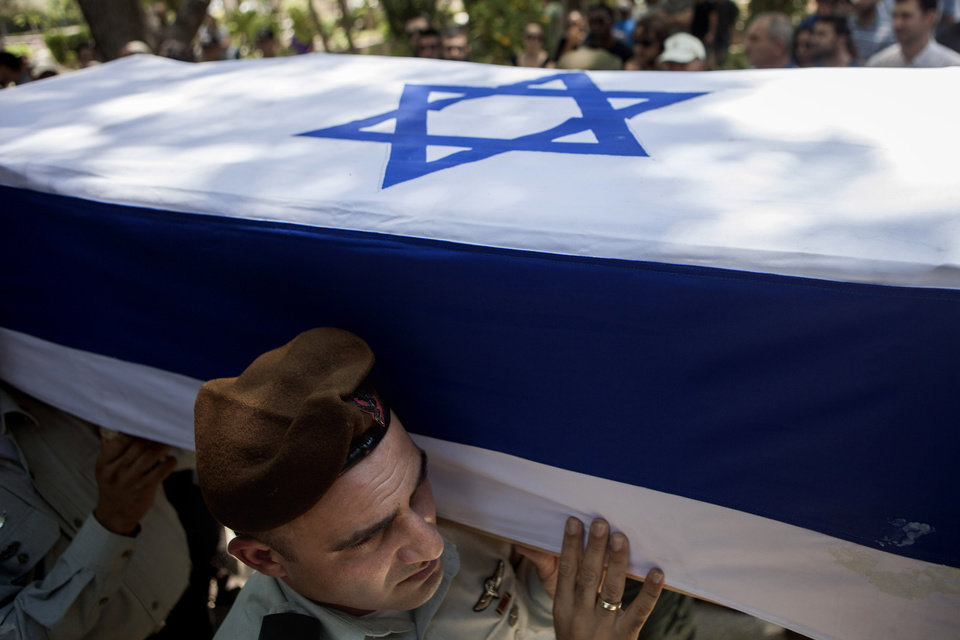 Photo - Israeli soldiers carry the coffin of Maj. Tzafrir Bar-Or, 32, one of 13 solider's who were killed in several separate incidents in Shijaiya on Sunday, at the military cemetery in Holon, Monday, July 21, 2014. On Sunday, the first major ground battle in two weeks of Israel-Hamas fighting exacted a steep price, killing scores of Palestinians and more than a dozen Israeli soldiers and forcing thousands of terrified Palestinian civilians to flee their devastated Shijaiyah neighborhood, which Israel says is a major source for rocket fire against its civilians. The 13 Israeli soldiers were killed in Shijaiya, in gun battles and rocket attacks. In the deadliest, Gaza fighters detonated a bomb near an armored personnel carrier, killing seven soldiers inside, the army said. In another incident, three soldiers were killed when they became trapped in a burning building, it said. (AP Photo/Dan Balilty)