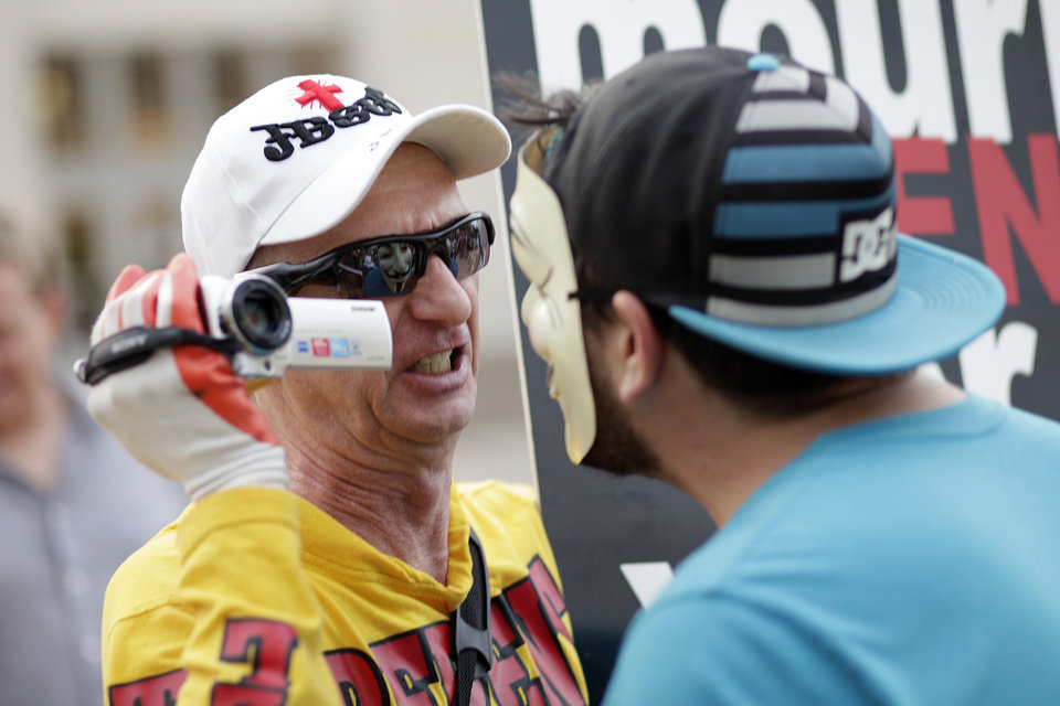 Photo - Brother Larry, of the Oklahoma Street Preachers, left, argues with Michael Jensen, right, of Edmond, during the protest of a Black Mass at the Civic Center Music Hall, Sunday, Sept. 21, 2014.  Photo by Garett Fisbeck, For The Oklahoman