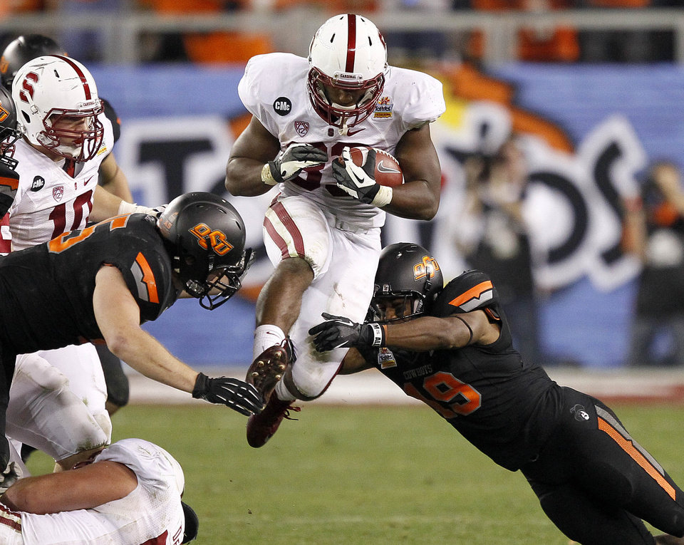 Stanford running back Stepfan Taylor, center, is tackled by Oklahoma State cornerback Brodrick Brown, right, and linebacker Caleb Lavey, left, during the second half of the Fiesta Bowl NCAA college football game Monday, Jan. 2, 2012, in Glendale, Ariz. (AP Photo/Matt York)