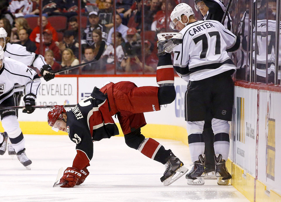 Photo - Phoenix Coyotes' Oliver Ekman-Larsson (23), of Sweden, gets upended by Los Angeles Kings' Jeff Carter (77) near the boards during the first period of an NHL hockey game, Tuesday, Jan. 28, 2014, in Glendale, Ariz. (AP Photo/Ross D. Franklin)