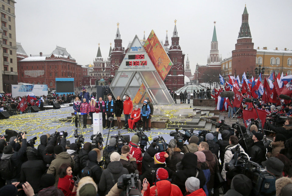 Photo - Moscow's Mayor Sergei Sobyanin, center, stands surrounded by a crowd of various sports enthusiasts waving Russian and Moscow flags during a ceremony of the launching the one-year count down clock for the upcoming 2014 Sochi Olympics, in Moscow, Russia, Thursday, Feb. 7, 2013. (AP Photo/Mikhail Metzel)