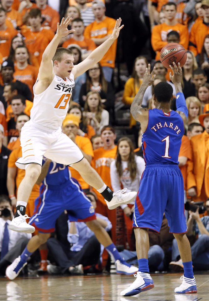 Photo - Oklahoma State 's Phil Forte (13) defends on Kansas' Naadir Tharpe (1) during the college basketball game between the Oklahoma State University Cowboys (OSU) and the University of Kanas Jayhawks (KU) at Gallagher-Iba Arena on Wednesday, Feb. 20, 2013, in Stillwater, Okla. Photo by Chris Landsberger, The Oklahoman