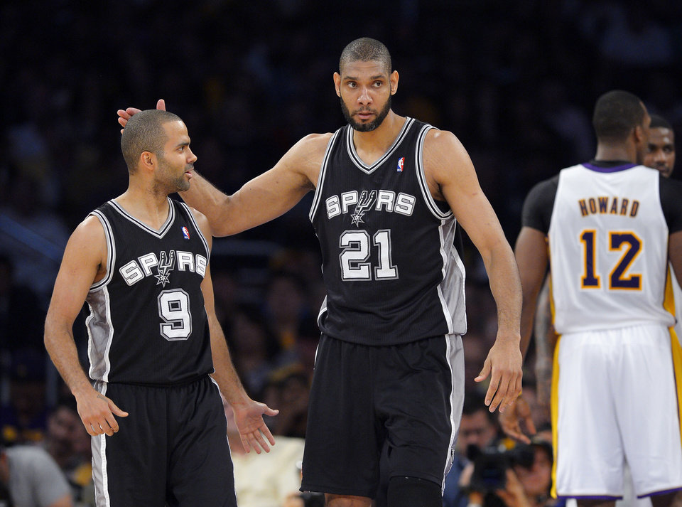 Photo - San Antonio Spurs forward Tim Duncan (21) pats guard Tony Parker (9), of France, on the head after he scored as Los Angeles Lakers center Dwight Howard (12) faces away during the first half in Game 4 of a first-round NBA basketball playoff series, Sunday, April 28, 2013, in Los Angeles. (AP Photo/Mark J. Terrill)