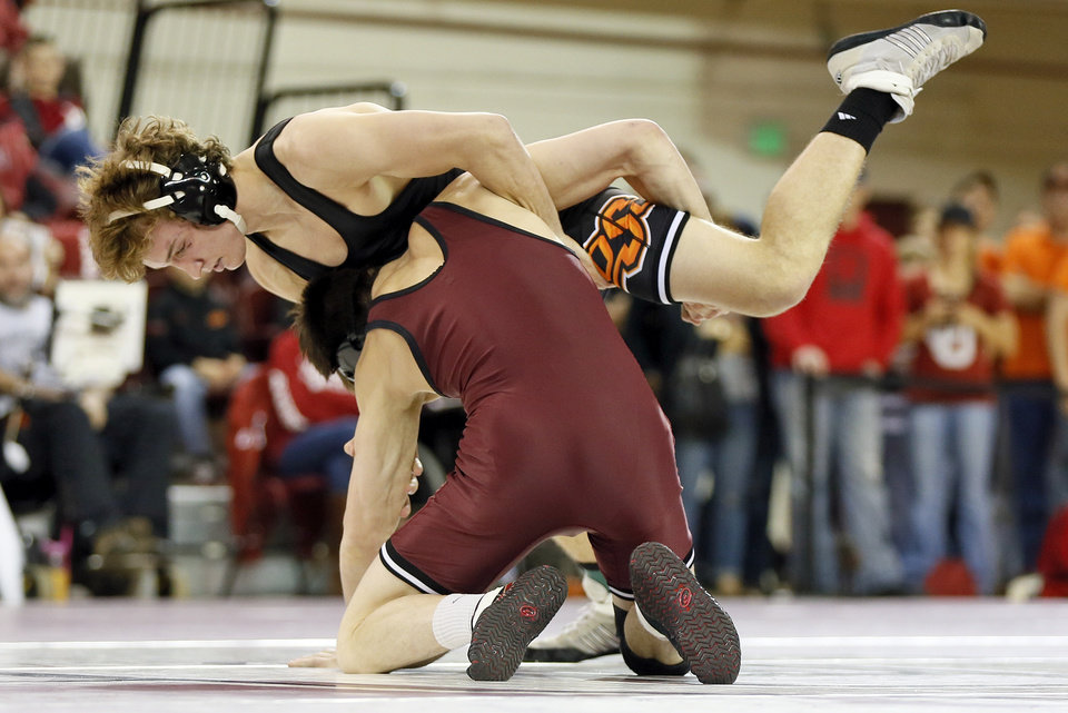 Photo - OSU's Anthony Collica, top, wrestles OU's Nick Lester in the 141-pound match during the Bedlam wrestling dual between the Oklahoma State Cowboys and the Oklahoma Sooners at McCasland Field House in Norman, Okla., Sunday, Dec. 1, 2013. OU won the dual, 16-15. Photo by Nate Billings, The Oklahoman