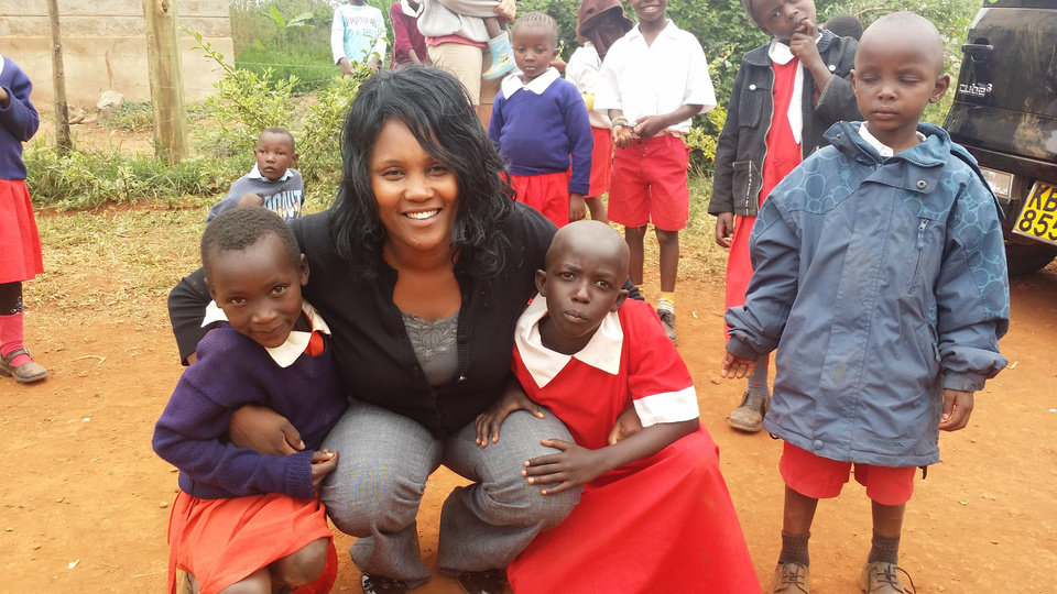Photo -  Eunice Menja, founder of Upendo Kids International, poses with two children whose education the organization sponsors. Photo provided