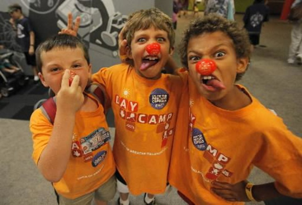 Photo -  Ashton Pirtle, 7, Wesley Canfield, 9, and Zander Baker, 8, pose for a photo wearing their clown noses after a Science Live show att the Science Museum of Oklahoma, Wednesday, June 27, 2012. Ringling Bros. clowns showed viewers the science behind circus performance. Photo by Garett Fisbeck, The Oklahoman