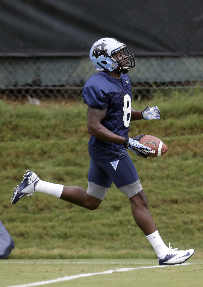 Photo - In this photo taken Friday, Aug. 1, 2014, North Carolina tailback T.J. Logan (8) runs the ball during an NCAA football practice in Chapel Hill, N.C. North Carolina has optimism from a strong finish and motivation from watching a rival's surprise run to the Atlantic Coast Conference championship game. (AP Photo/Gerry Broome)