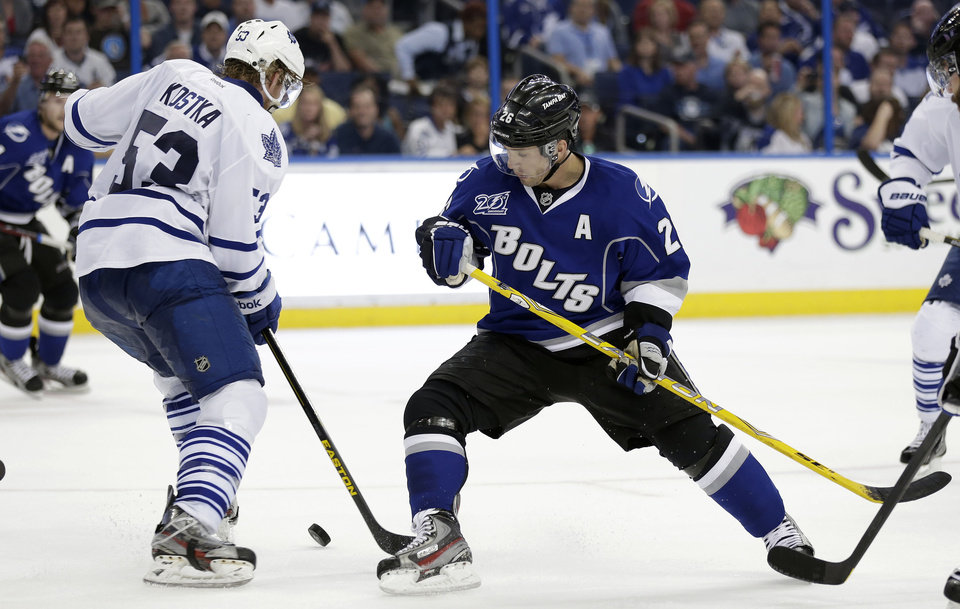 Photo - Tampa Bay Lightning right wing Martin St. Louis (26) kicks the puck away from Toronto Maple Leafs defenseman Mike Kostka (53) during the third period of an NHL hockey game Wednesday, April 24, 2013, in Tampa, Fla. The Lightning won the game 5-2. (AP Photo/Chris O'Meara)