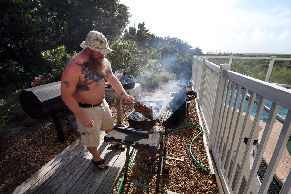 Photo - Shawn Jewell grills spare ribs outside the the home where he is vacationing with friends in Avon, N.C., on Hatteras Island as Tropical Storm Arthur comes up the up the Atlantic coast on Wednesday, July 2, 2014.  He and his friends had begun packing up their belongings and would be ready to leave if an evacuation is called for.   (AP Photo/The Virginian-Pilot, Steve Earley)  MAGS OUT