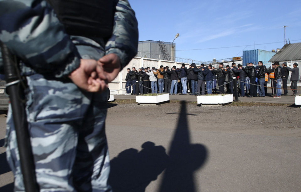 Photo - People detained by police line up for identity checks at a vegetable warehouse in Moscow's outskirts, Monday, Oct. 14, 2013. Police in Moscow rounded up over a thousand employees of a vegetable warehouse on Monday, a day after riots on the Russian capital's southern outskirts. (AP Photo/ Denis Tyrin)