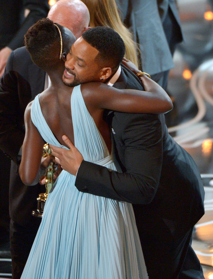 Photo - Will Smith, right, embraces Lupita Nyong'o after announcing that