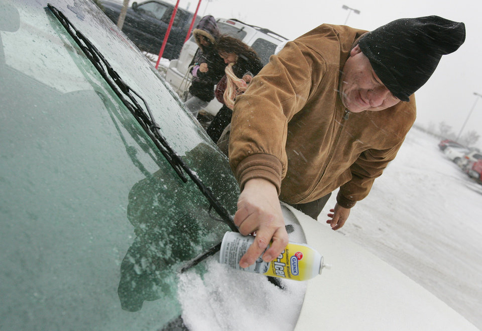Photo - Gary Oberly hits his wind shield wipers with a can of de-icer as he tries to get them working outside the Norman Target Thurs. Dec. 24, 2009. Photo by Jaconna Aguirre, The Oklahoman.