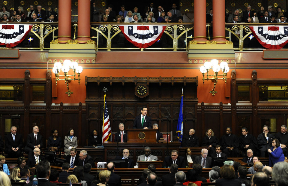 "Photo - Connecticut Gov. Dannel P. Malloy, center, at podium, speaks to members of the House and the Senate in his State of the State address at the Capitol in Hartford, Conn., Wednesday, Jan. 9, 2013. Malloy urged state lawmakers Wednesday to work with him to prevent future tragedies like the Sandy Hook Elementary School shooting, but stressed that ""more guns are not the answer.""  Legislators also must grapple with a projected deficit of about $1.2 billion. (AP Photo/Jessica Hill)"