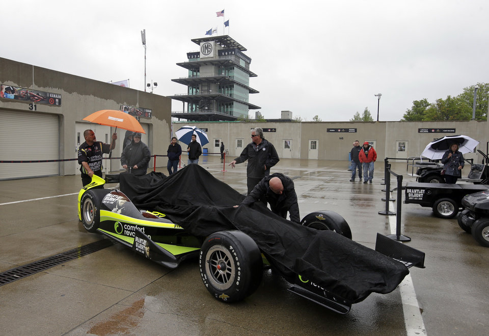 Photo - The crew of the car driven by Sage Karam, pushes the car through the garage area as rain halted practice for the Indianapolis 500 IndyCar auto race at the Indianapolis Motor Speedway in Indianapolis, Wednesday, May 14, 2014. (AP Photo/Darron Cummings)