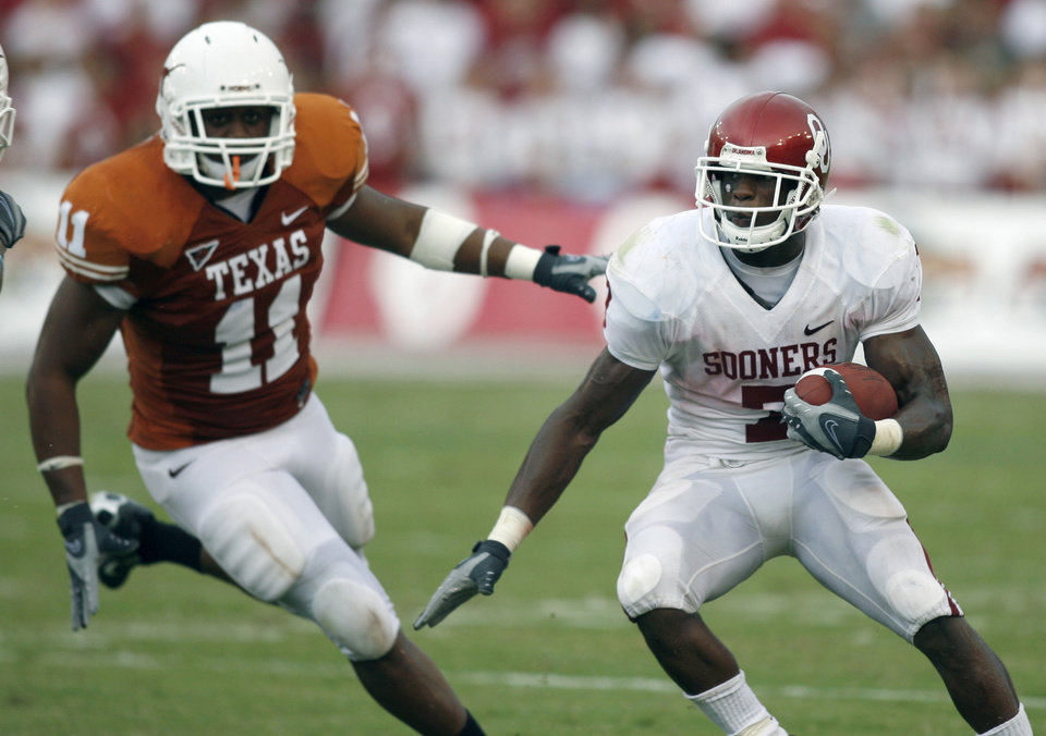 Photo - OU: University of Oklahoma running back DeMarco Murray (7) runs against University of Texas in the fourth quarter of their NCAA college football game, Saturday, Oct. 6, 2007, in Dallas. DeMarco picked up 129 yards in Oklahoma's 28-21 win.  At left is Texas linebacker Jared Norton (11). (AP Photo/Mike Stone) ORG XMIT: DNB127