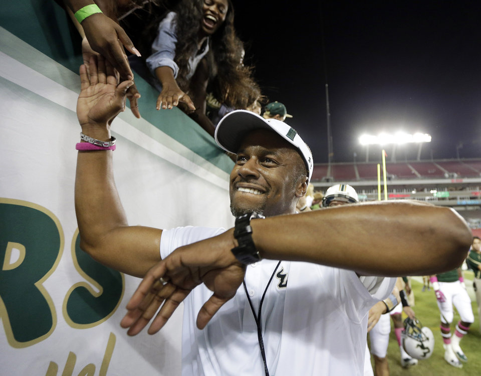 Photo - FILE - In this Oct. 5, 2013, file photo, South Florida head coach Willie Taggart celebrates with fans after the team defeated Cincinnati during an NCAA college football game in Tampa, Fla. Now that Chris Petersen has left Boise State for Washington, college football needs another coach from outside the so-called Big 5 conferences that will have his name come up for almost every big job. (AP Photo/Chris O'Meara, File)