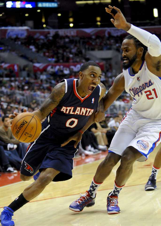 Atlanta Hawks guard Jeff Teague (0) drives on Los Angeles Clippers center Ronny Turiaf (21), of France, while looking to the basket in the first half of an NBA basketball game on Sunday, Nov. 11, 2012, in Los Angeles. (AP Photo/Gus Ruelas)