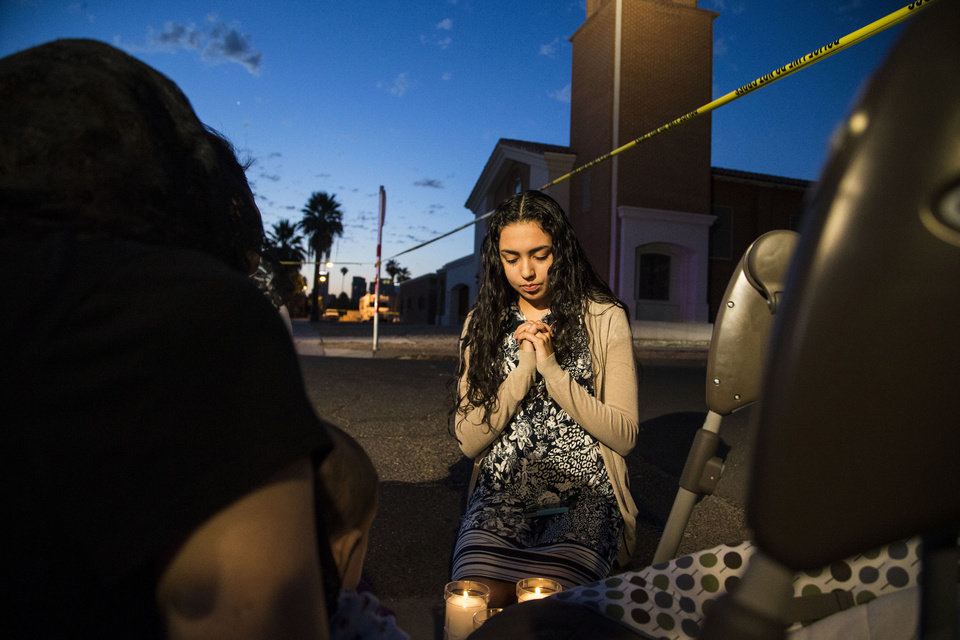 Photo - Mater Misericordiae (Mother of Mercy) Mission, church member, Kirsten Duarte, center, prays while Phoenix Police investigate a shooting at the church on Wednesday, June 11, 2014 in Phoenix.  Police say one priest was shot to death and another is injured after an attack at the church in downtown Phoenix. The Roman Catholic Diocese of Phoenix on Thursday identified the slain priest as the Rev. Kenneth Walker and the injured priest as the Rev. Joseph Terra. (AP Photo/The Arizona Republic, Nick Oza)  MARICOPA COUNTY OUT; MAGS OUT; NO SALES