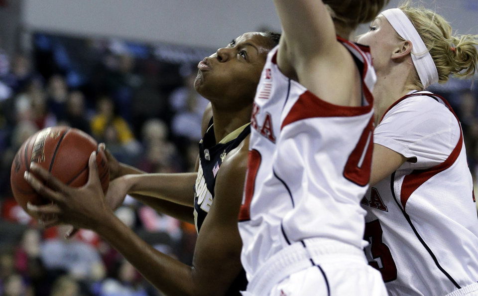 Photo - Purdue forward Drey Mingo, left, drives to the basket against Nebraska guard Lindsey Moore, center, forward Emily Cady during the first half of an NCAA college basketball game in the Big Ten Conference tournament in Hoffman Estates, Ill., on Saturday, March 9, 2013. (AP Photo/Nam Y. Huh)