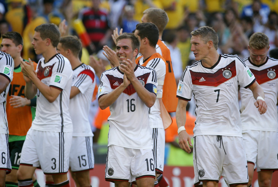 Photo - Germany's Philipp Lahm, center, smiles at the end of  the World Cup quarterfinal soccer match between Germany and France at the Maracana Stadium in Rio de Janeiro, Brazil, Friday, July 4, 2014. Germany won the match 1-0.  . (AP Photo/David Vincent)