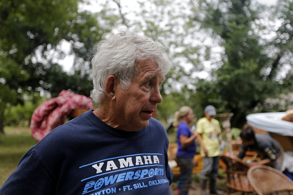 Photo - Dennis Easter looks at his damaged property after the West Cache Creek overflowed flooding the area in Cache, Okla., Sunday, May 24 2015.  Easter and his family were rescued from thier roof early Sunday as floods surrounded the home. Photo by Sarah Phipps, The Oklahoman