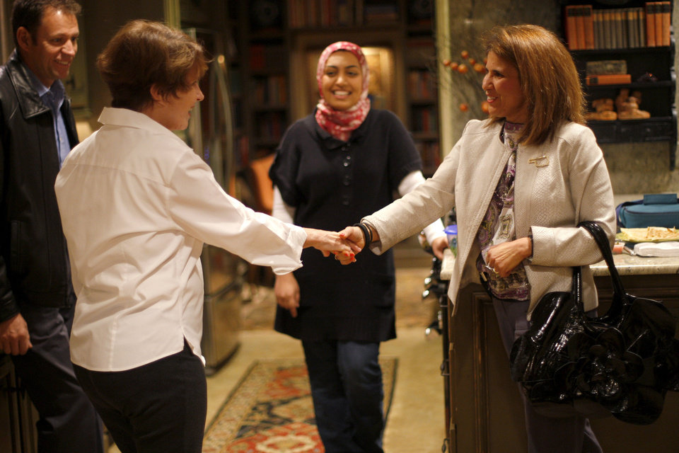 Photo - Marilyn Baragree greets Terri Angier, as Greg Smith, at left, and Sarah Albahadily watch as guests arrive for a recent Amazing Faiths interfaith dinner in the Edmond area. Photo by Bryan Terry, The Oklahoman   BRYAN TERRY - THE OKLAHOMAN