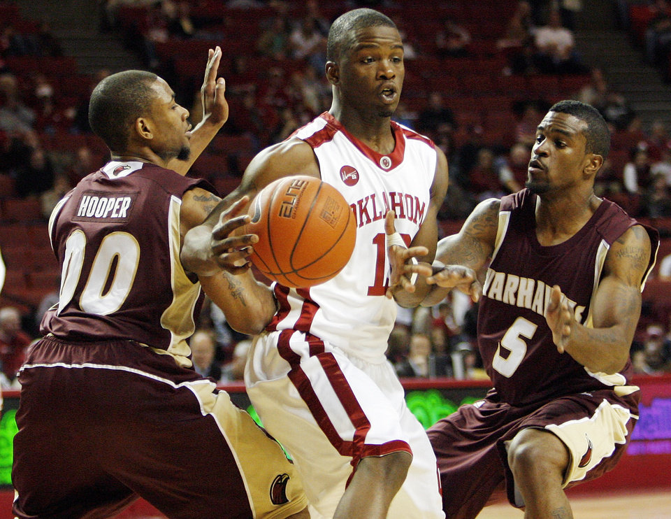 Photo - OU's Willie Warren (13) tries to move between the defense of ULM's Tony Hooper (00) and Dynile Forbes (5) during the first half of the men's college basketball game between the Oklahoma Sooners and Louisiana-Monroe at Lloyd Noble Center in Norman, Okla., Tuesday, Nov. 17, 2009. Photo by Nate Billings, The Oklahoman