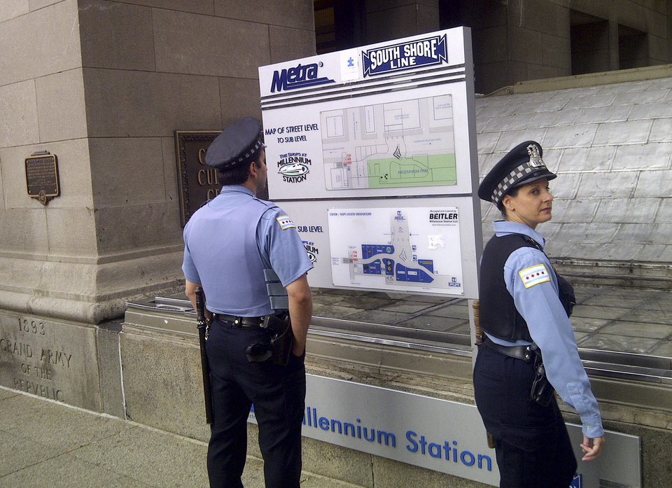 Photo -   A pair of Chicago police officers stand outside the Metra commuter line's Millennium Station near Chicago's Grant Park Monday morning, May 21, 2012. Commuter traffic appears to be down in Chicago as the NATO summit enters its second and final day. Many companies heeded official advice and are let their workers stay home for the day. (AP Photo/Ryan J. Foley)