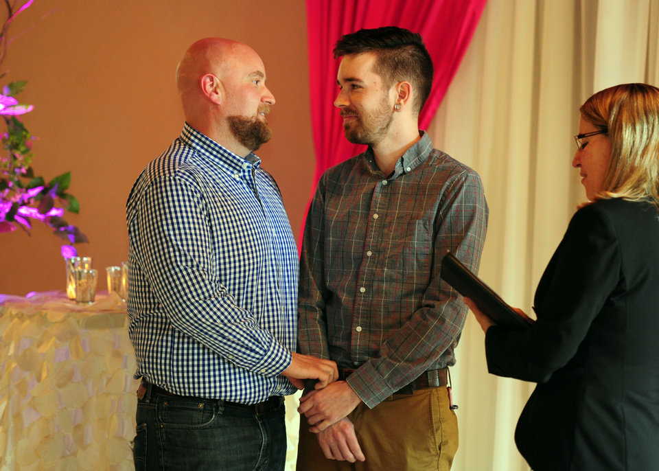 Photo - Jeff Salchenberg, left, and Paul Reinwand get married by Celebrant Holly Pruett, right, at the Melody Ballroom in Portland, Ore., on Monday, May. 19, 2014. Federal Judge Michael McShane released an opinion on Oregon's Marriage Equality lawsuit that grants gay and lesbian couples the freedom to marry in Oregon. (AP Photo/Steve Dykes)