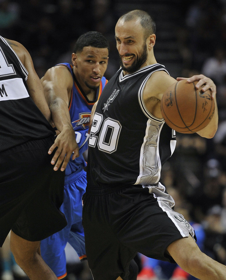 Photo - San Antonio Spurs guard Manu Ginobili, right, of Argentina, drives around Oklahoma City Thunder forward Andre Roberson during the first half an NBA basketball game, Thursday, Dec. 25, 2014, in San Antonio. (AP Photo/Darren Abate)