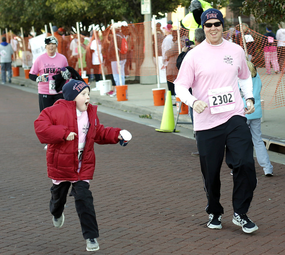 Larry Young, of Oklahoma City, and his son, Jake, 7, cross the finish line during the 19th Annual Oklahoma City Race for the Cure at Chickasaw Bricktown Ballpark in Oklahoma City on Saturday. PHOTO BY GARETT FISBECK, THE OKLAHOMAN
