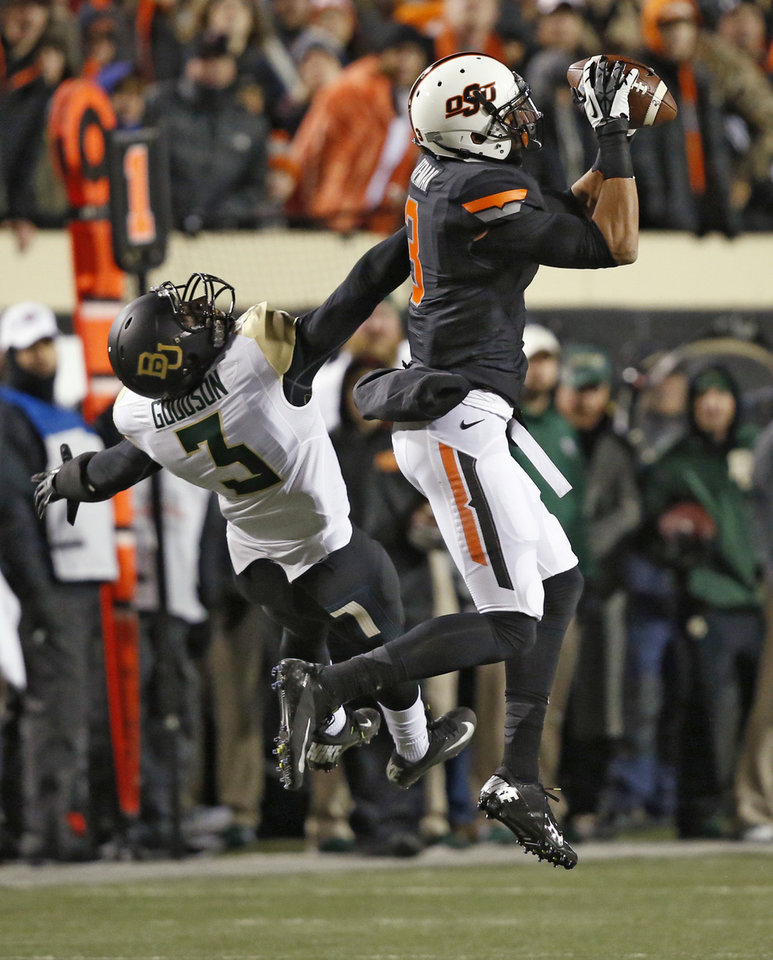 Photo - Oklahoma State wide receiver Marcell Ateman (3) grabs a pass in front of Baylor cornerback Demetri Goodson (3) in the first quarter of an NCAA college football game in Stillwater, Okla., Saturday, Nov. 23, 2013. (AP Photo/Sue Ogrocki)