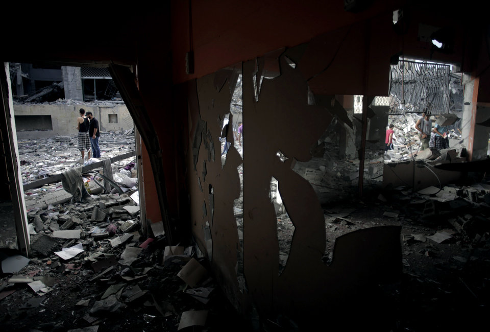 Photo - Palestinians inspect the damage to the Italian Complex high-rise following several late night Israeli airstrikes in Gaza City, Tuesday, Aug. 26, 2014. Israel bombed two Gaza City high-rises with dozens of homes and shops Tuesday, collapsing the 15-story Basha Tower and severely damaging the Italian Complex in a further escalation in seven weeks of cross-border fighting with Hamas. (AP Photo/Khalil Hamra)