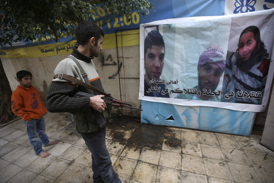 Photo - A Lebanese anti-Syrian regime gunman looks at a poster shows a portrait of Malek Haj Deeb, 20, left, with his two friends who were three of several of the young Lebanese men who were killed in neighboring Syria's civil war last week, in the poor neighborhood of Mankoubeen, in the northern port city of Tripoli, Lebanon, Wednesday Dec. 5, 2012. The families of several of the young Lebanese men who were killed in Syria last week say their sons were more interested in fashion and swimming holidays than fighting in a foreign war. But when the men's corpses turned up in Syria, the government in Damascus said they were part of the stream of foreign jihadists pouring into the country to fight alongside rebels. (AP Photo/Hussein Malla)