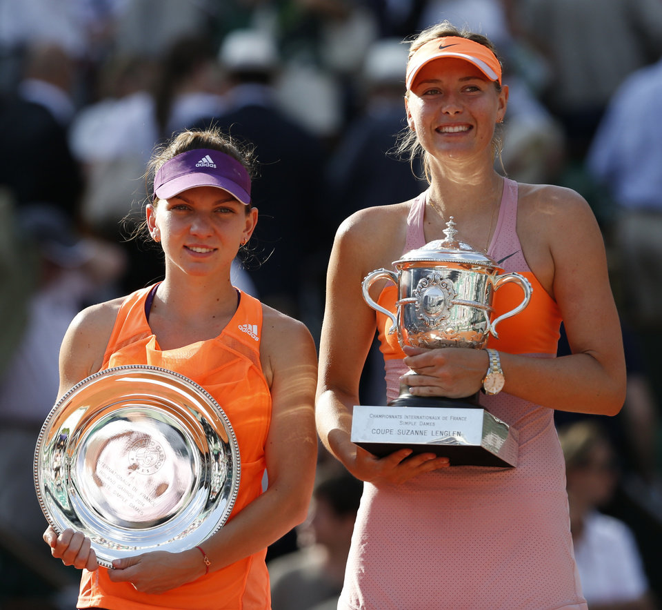 Photo - Romania's Simona Halep, left, holds the runner-up trophy, when posing with Russia's Maria Sharapova, right, who won the final of the French Open tennis tournament at Roland Garros stadium, in Paris, France, Saturday, June 7, 2014. Sharapova won in three sets 6-4, 6-7, 6-4. (AP Photo/Darko Vojinovic)