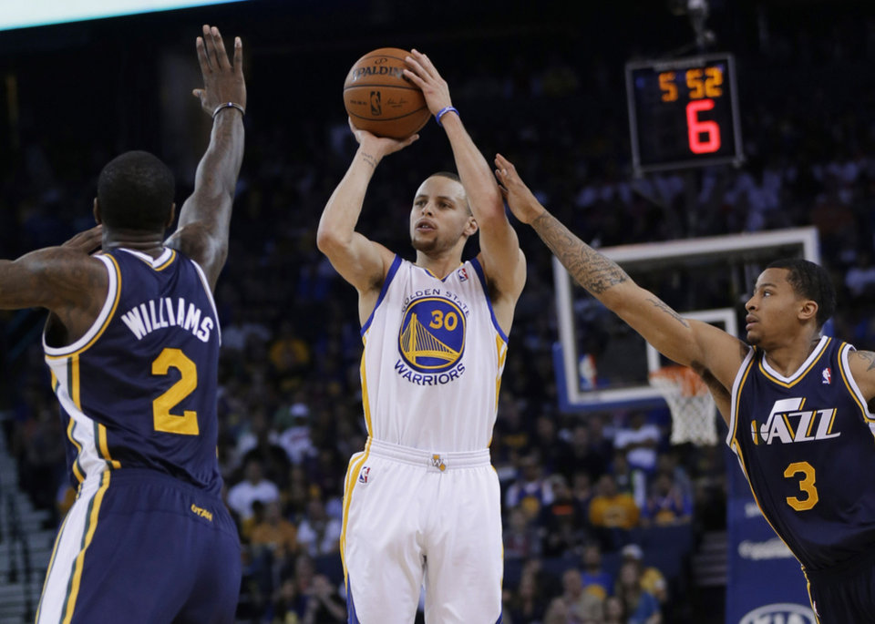 Photo - Golden State Warriors guard Stephen Curry (30) shoots between Utah Jazz forward Marvin Williams (2) and guard Trey Burke (3) during the first half of an NBA basketball game Sunday, April 6, 2014, in Oakland, Calif. (AP Photo/Marcio Jose Sanchez)