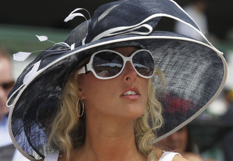 Photo - Stephanie Harris, from Lexington, Ky., waits for the start of a race in the grandstand before the 138th Kentucky Derby horse race at Churchill Downs, Saturday, May 5, 2012, in Louisville, Ky. The Run for the Roses draws them to Churchill Downs. But what race goers wear is as much a spectacle in itself. (AP Photo/Michael Conroy) ORG XMIT: NY221
