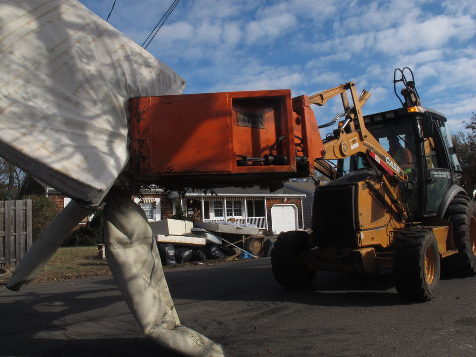 Public works crews in Point Pleasant N.J. remove the ruined contents of homes on Monday, Nov. 5, 2012. A new storm, this one a nor'easter, is expected Wednesday, raising fears of renewed damage along the already hard-hit Jersey shore. (AP Photo/Wayne Parry)
