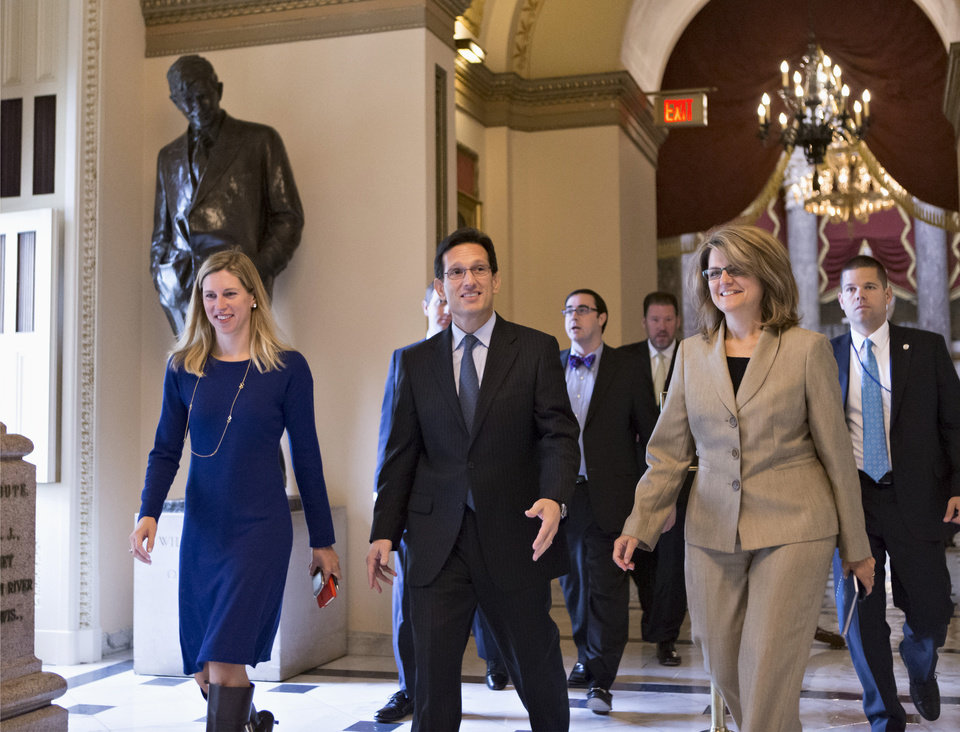 Photo - House Majority Leader Eric Cantor of Va., center, walks to the floor of the House on Capitol Hill in Washington, Friday, Sept. 27, 2013, as Congress continues to struggle over how to fund the government and prevent a possible shutdown.   (AP Photo/J. Scott Applewhite)