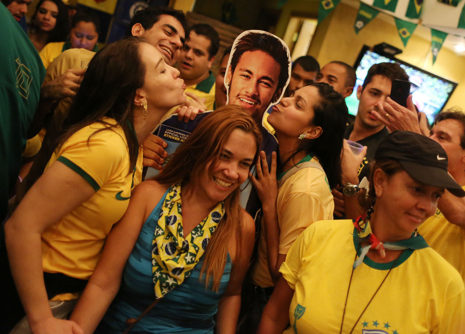 Photo - Soccer fans donning Brazil's national team colors pose for a picture with a life-size cutout of soccer star Neymar, after the World Cup match between Brazil and Cameroon, at the Copacabana beach, in Rio de Janeiro, Brazil, Monday, June 23, 2014. Neymar lived up to the expectations of the World Cup host nation Monday, scoring two goals as Brazil routed Cameroon 4-1 to reach the knockout stage as the top team in Group A. (AP Photo/Leo Correa)