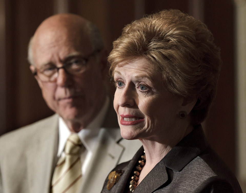 FILE - In this June 6, 2012 file photo, Sen. Pat Roberts, R-Kansas, ranking Republican on the Senate Agriculture Committee, listens at left as Committee Chair Sen. Debbie Stabenow, D-Mich. speaks about the farm bill during a news conference on Capitol Hill in Washington. (AP Photo/J. Scott Applewhite)