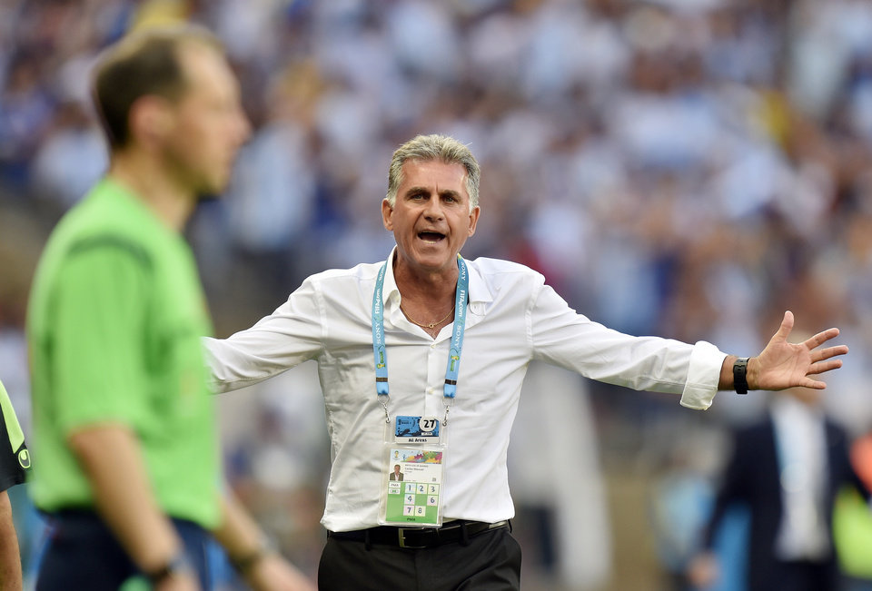 Photo - Iran's head coach Carlos Queiroz questions a linesman on a call during the group F World Cup soccer match between Argentina and Iran at the Mineirao Stadium in Belo Horizonte, Brazil, Saturday, June 21, 2014. Argentina defeated Iran 1-0. (AP Photo/Martin Meissner)