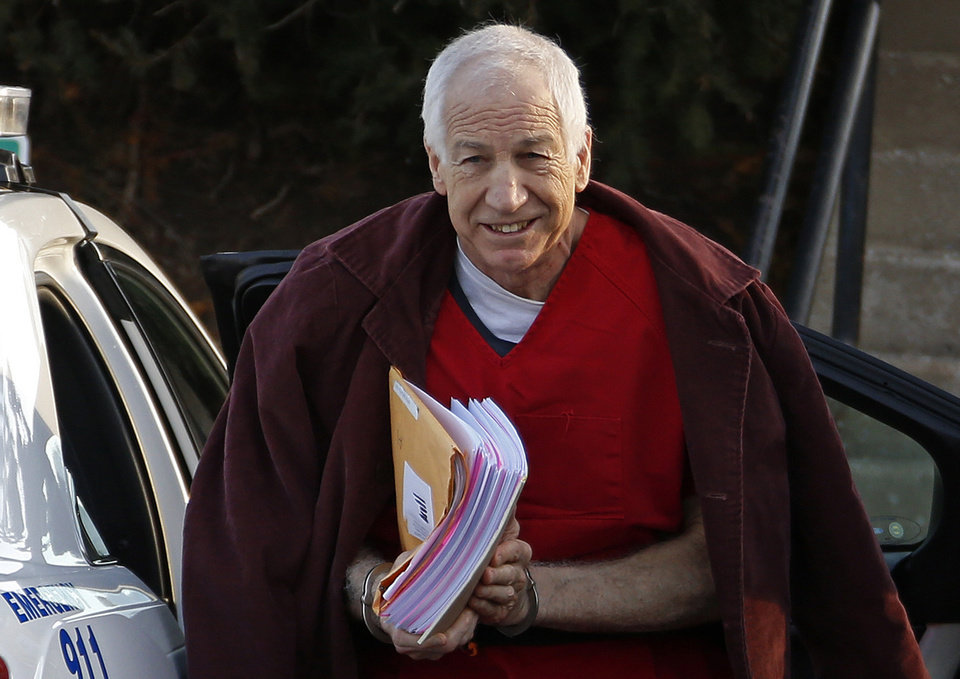 Photo - FILE - In this Jan. 10, 2013, file photo, former Penn State assistant football coach Jerry Sandusky arrives at the Centre County Courthouse for a post-sentencing hearing in Bellefonte, Pa. Penn State said Monday, Oct. 28, 2013 that it is paying $59.7 million to 26 young men over claims of child sexual abuse at the hands of  Sandusky. The university said it had concluded negotiations that have lasted about a year. The school said 23 deals are fully signed and three are agreements in principle. The school faces six other claims, and the university says it believes some do not have merit while others may produce settlements. Sandusky, 69, is serving a 30- to 60-year prison sentence at a state prison in southwestern Pennsylvania.  (AP Photo/Gene J. Puskar, File)