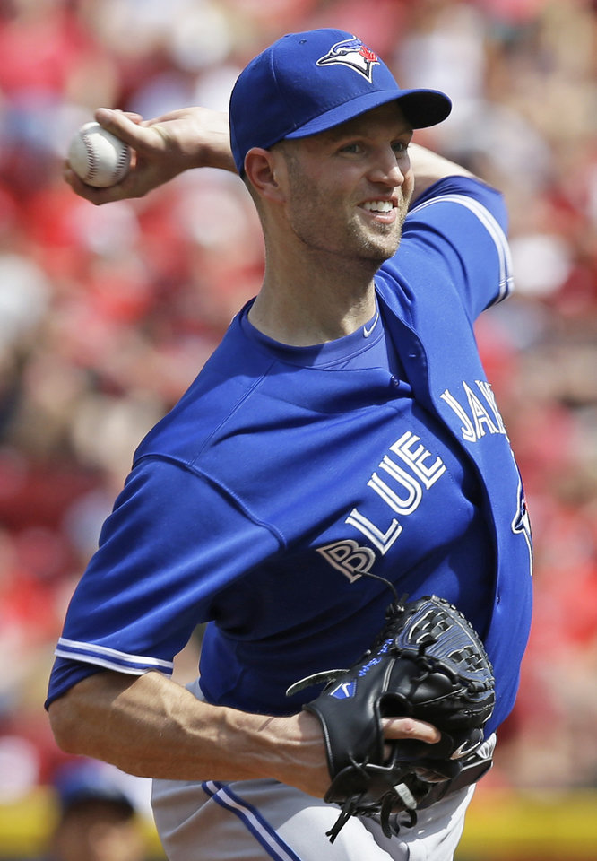 Photo - Toronto Blue Jays starting pitcher J.A. Happ throws against the Cincinnati Reds in the first inning of a baseball game, Saturday, June 21, 2014, in Cincinnati. (AP Photo/Al Behrman)