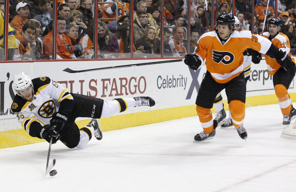 Photo - Boston Bruins' Kevan Miller, left, looks to pass the puck while falling as Philadelphia Flyers' Jay Rosehill, right, skates in during the second period of an NHL hockey game, Saturday, Jan. 25, 2014, in Philadelphia.  (AP Photo/Chris Szagola)