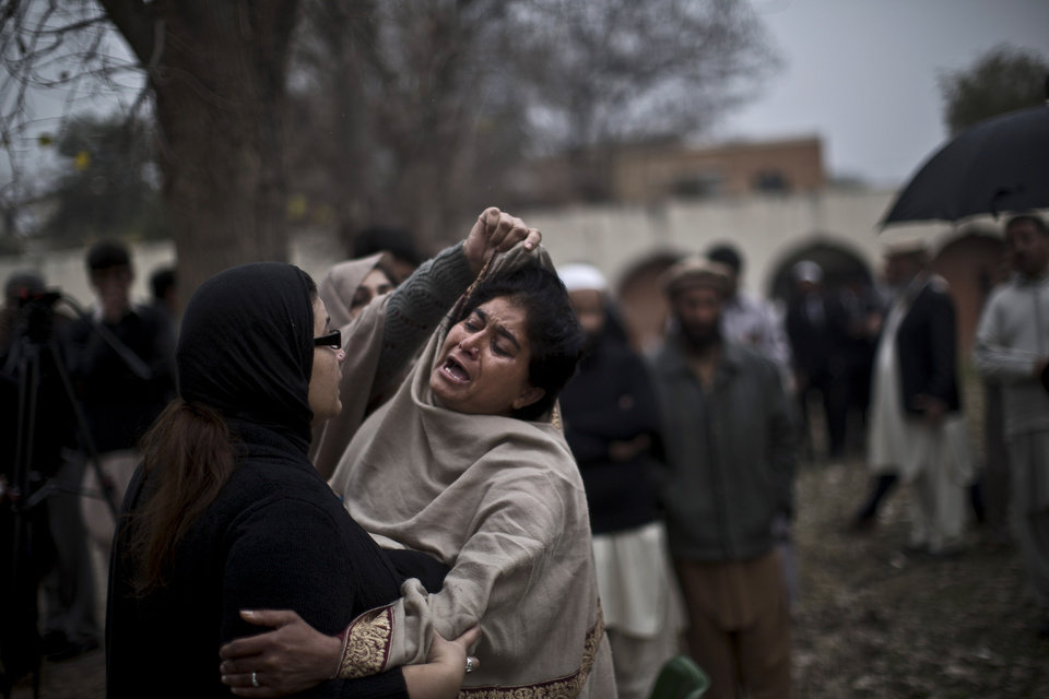 Photo - A Pakistani woman comforts a woman grieving outside a hospital's morgue, where the bodies of victims of a twin suicide bombing are, in Islamabad, Pakistan, Monday, March 3, 2014. Two suicide bombers blew themselves up at a court complex in the Pakistani capital on Monday, killing nearly a dozen and wounding scores in a rare terror attack in the heart of Islamabad, officials said. (AP Photo/Muhammed Muheisen)