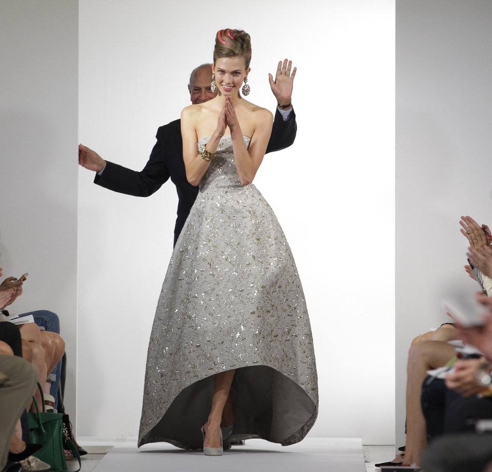 Photo -   Fashion designer Oscar de la Renta waves as the final model in his show claps and walks the runway at the conclusion of the presentation of the Oscar de la Renta Spring 2013 collection at Fashion Week in New York, Tuesday, Sept. 11, 2012. (AP Photo/Kathy Willens)